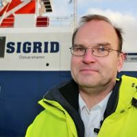 En man med glasögon framför fartyget.