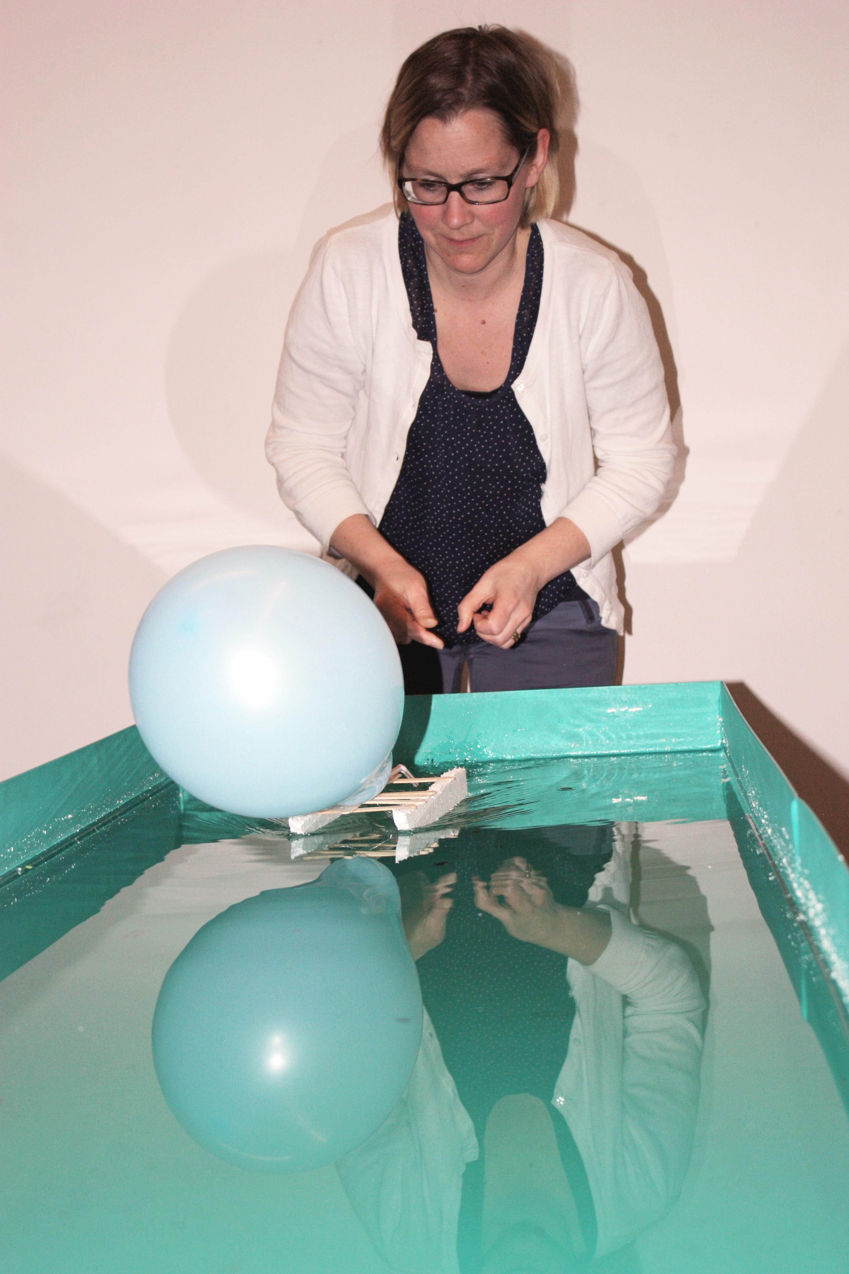 En kvinna står framför en låda med vatten.