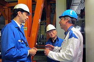 Tre män med hjälm pratar med varandra. Foto: SKB.