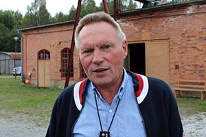 En man står framför en tegelbyggnad. Foto: SKB.
