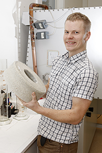 En man håller i ett block med bentonilera. Foto: Curt-Robert Lindqvist.