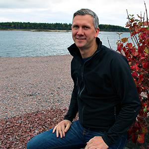 Johan Molin sitter ned vid strandkant.